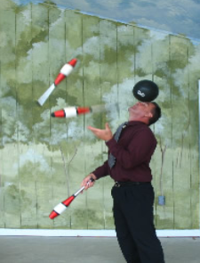 Man juggling red and white pins while balancing a black bowling ball on his forehead