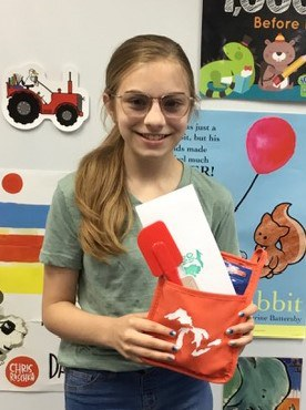 Young woman holding the Cooking challenge prize, a rubber spatula, red Michigan Mitten hot mitt and $10 gift certificate to OHMi