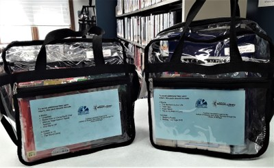 Two exploration packs, clear messenger bags containing books and activities